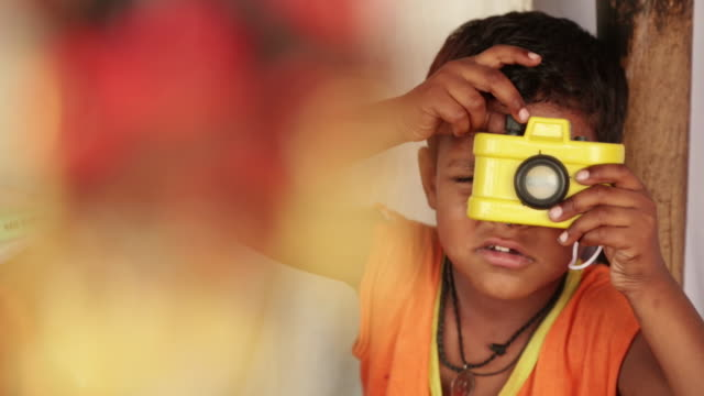 boy playing with plastic toy camera, haridwar, uttarakhand, india - spielzeug stock-videos und b-roll-filmmaterial