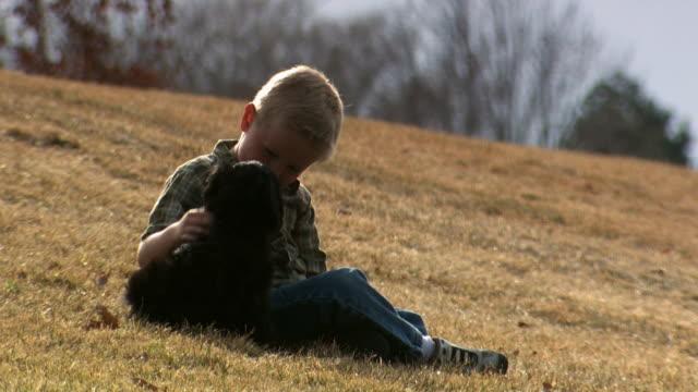 boy playing with puppy outdoors - andere clips dieser aufnahmen anzeigen 1166 stock-videos und b-roll-filmmaterial