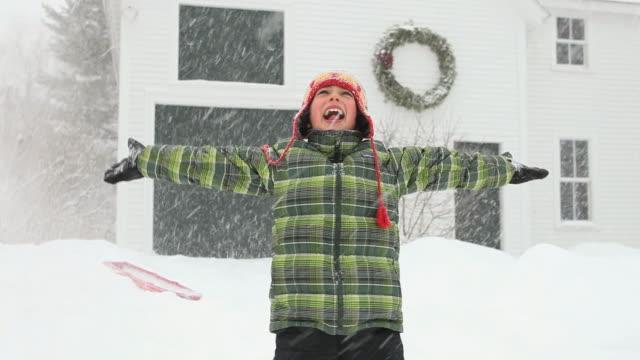 vídeos de stock, filmes e b-roll de ms tu zo boy playing with snow during snowstorm  / yarmouth, maine, usa - braço humano