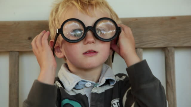 ms boy playing with thick glasses / copenhagen, sjaelland, denmark - occhiali da vista video stock e b–roll