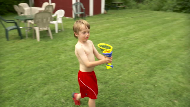 WS PAN Boy (6-7) playing with toy in playground / Stowe, Vermont, USA