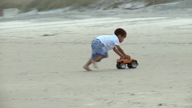 WS TS PAN Boy (2-3) playing with toy jeep on beach, girl (4-5) sitting on deckchair / Jacksonville, Florida, USA