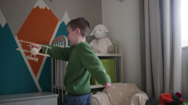 Boy playing with toy model plane
