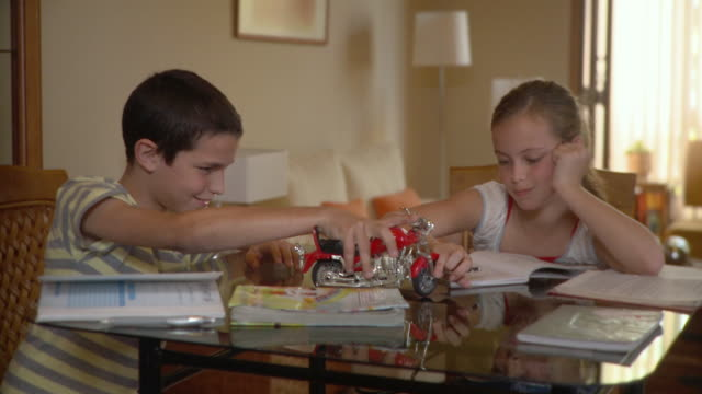 MS Boy (10-11) playing with toy while girl studying / Havana, Cuba