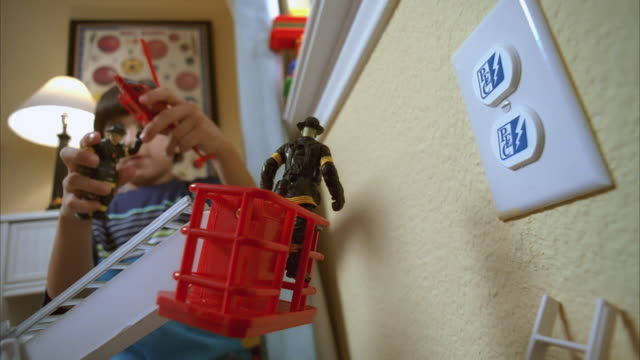 ms slo mo boy playing with toys next to wall outlet / kyle, texas, usa - plug socket stock videos and b-roll footage