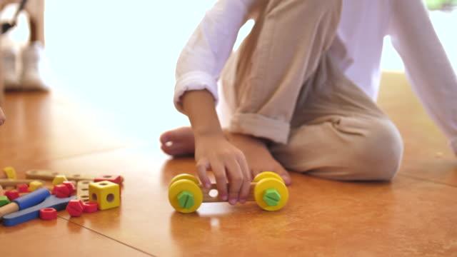 vidéos et rushes de garçon jouant le jouet de voiture de bois sur l'étage - pièce intérieur de maison