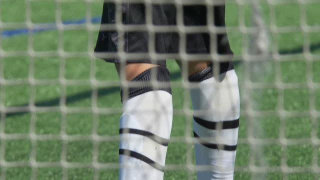 a boy playing youth soccer football goalie goalkeeper on a turf grass field wearing green gloves. - slow motion - soccer glove stock videos and b-roll footage