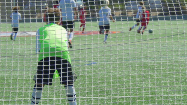 a boy playing youth soccer football goalie goalkeeper on a turf grass field wearing green. - slow motion - soccer glove stock videos and b-roll footage