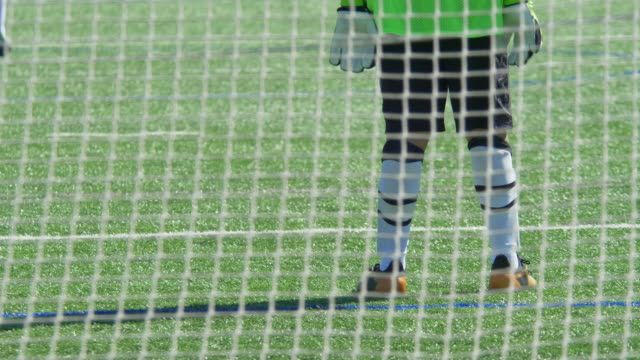 vídeos de stock e filmes b-roll de a boy playing youth soccer football goalie goalkeeper on a turf grass field wearing green. - slow motion - campo de futebol