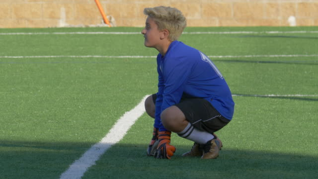 a boy playing youth soccer football goalie goalkeeper on a turf grass field. - slow motion - soccer goalkeeper stock videos & royalty-free footage