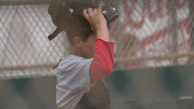 boy plays catcher and catching in a little league baseball game. - slow motion - 野球用グローブ点の映像素材/bロール