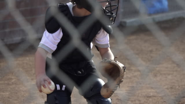 A boy plays catcher in a little league baseball game. - Slow Motion