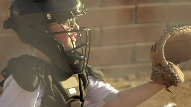 a boy plays catcher in a little league baseball game. - baseballspieler stock-videos und b-roll-filmmaterial