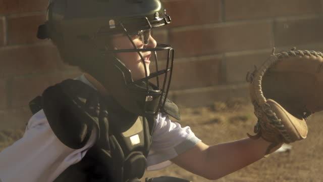 A boy plays catcher in a little league baseball game.
