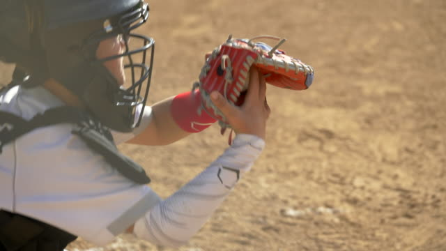 stockvideo's en b-roll-footage met boy plays catcher in a little league baseball game. - honkbal teamsport