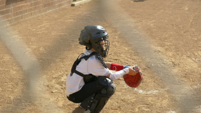 Boy plays catcher in a little league baseball game.