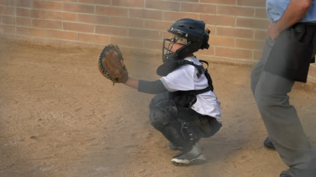 Boy plays catcher in a little league baseball game.