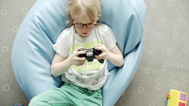vídeos de stock, filmes e b-roll de o menino joga o console - meninos