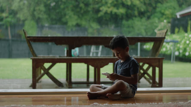boy plays on phone while rain falls outside - indoors stock videos & royalty-free footage