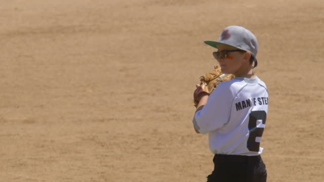 boy plays pitcher in a little league baseball game. - baseballspieler stock-videos und b-roll-filmmaterial
