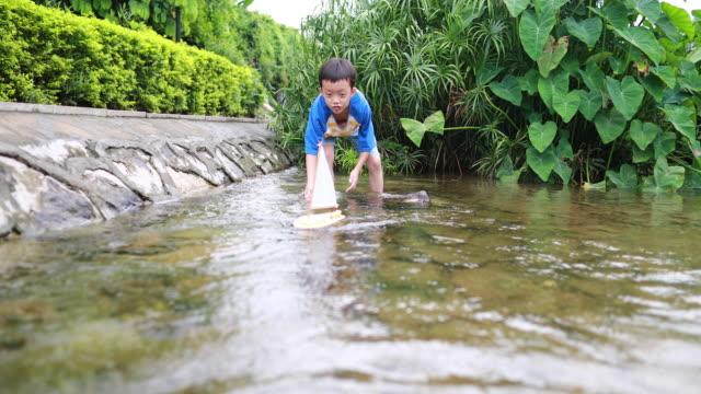 少年は水の中でおもちゃのヨットで遊ぶ - おもちゃ点の映像素材/bロール