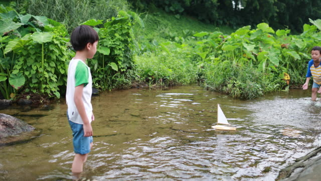 boy plays with toy sailboat in water - small boat stock videos & royalty-free footage