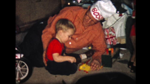 1957 boy plays with xmas presents with grandpa - innocenza video stock e b–roll