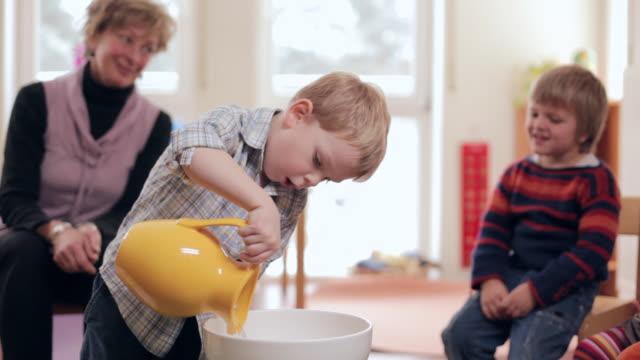 vídeos de stock e filmes b-roll de ms boy pouring water with water jug in bowl / potsdam, brandenburg, germany - tigela