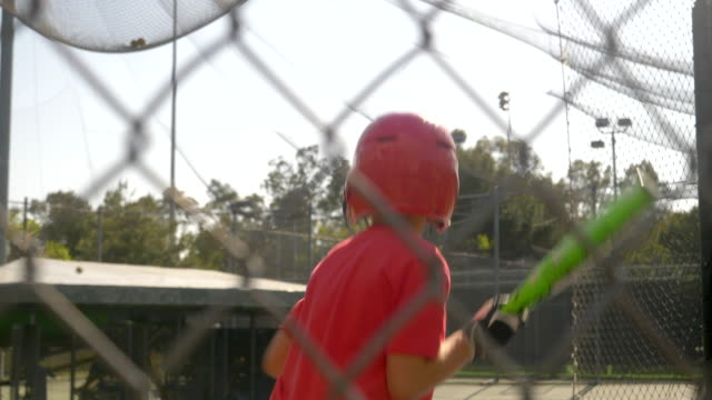 a boy practices little league baseball at the batting cages and bunting the ball. - slow motion - gabbia di battuta video stock e b–roll