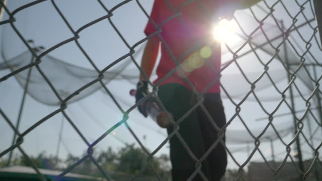 a boy practices little league baseball at the batting cages and walks out leaving the cage. - slow motion - gabbia di battuta video stock e b–roll
