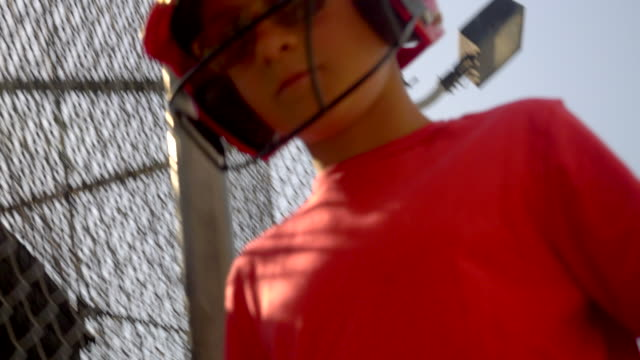 a boy practices little league baseball at the batting cages and walks in entering the cage. - slow motion - gabbia di battuta video stock e b–roll