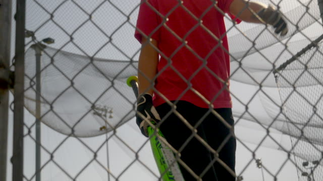 a boy practices little league baseball at the batting cages and walks out leaving the cage. - gabbia di battuta video stock e b–roll