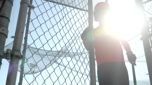 a boy practices little league baseball at the batting cages and walks in entering the cage. - slow motion - filmed at 180 fps - gabbia di battuta video stock e b–roll