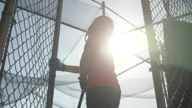 a boy practices little league baseball at the batting cages and walks out leaving the cage. - slow motion - filmed at 180 fps - 門点の映像素材/bロール