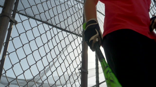 a boy practices little league baseball at the batting cages and walks out leaving the cage. - slow motion - filmed at 180 fps - gabbia di battuta video stock e b–roll