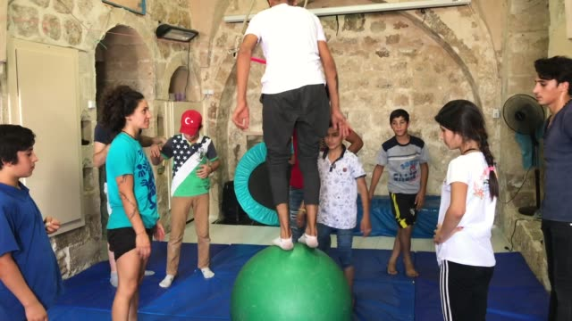 a boy practices walking on a ball during an acrobatics workshop at the istasyon sirkhane center on july 24 2018 in mardin turkey the circus school or... - stilt house stock videos & royalty-free footage
