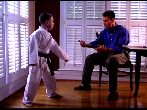 Boy practicing karate with father
