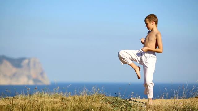 vídeos de stock, filmes e b-roll de menino praticando artes marciais na costa - karate