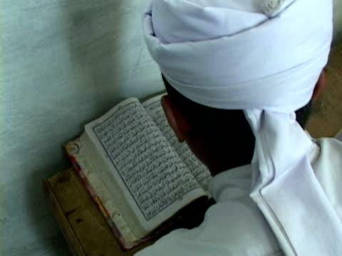 cu ha boy praying at madrassa with koran, shitral valley, north west province, pakistan - koran stock videos & royalty-free footage