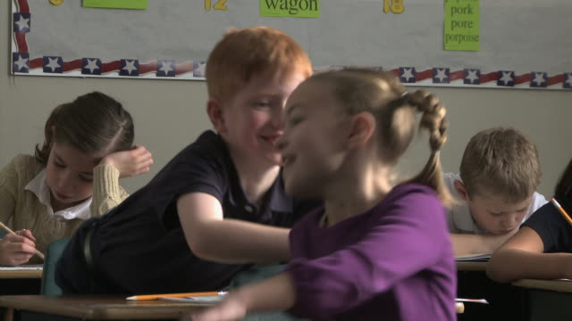 boy pulling a girls pig tail in class - bullying stock videos & royalty-free footage