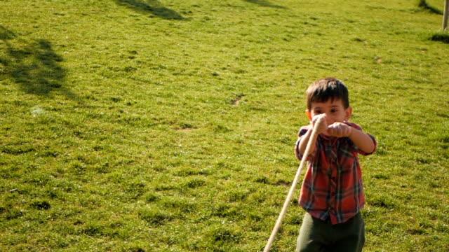 vídeos de stock, filmes e b-roll de menino que puxa uma corda e que joga o cabo de guerra no parque - cordão