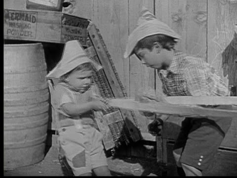 1924 b/w montage ws ms boy (jackie lucas) pulling back slingshot while another boy adjusts rock in it / rock flying through doorway of house / rock hitting man (charles murray) in head / boy looking surprised / usa - silent film stock videos & royalty-free footage