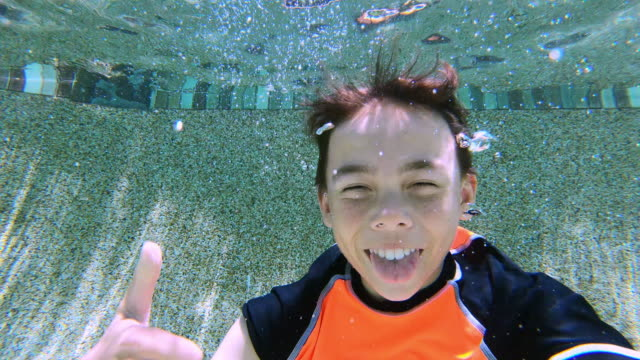 boy pulling faces underwater - gente comune video stock e b–roll