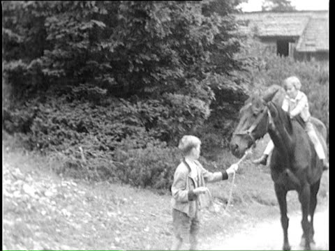 1937 b/w ms boy (10-11) pulling horse carrying girl (8-9) / bavaria, germany - pferderitt stock-videos und b-roll-filmmaterial