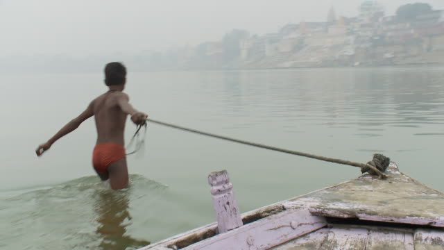 A boy pulls a boat in the Ganges River.