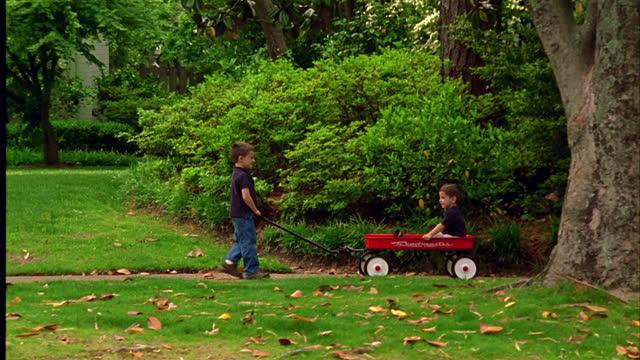 vidéos et rushes de a boy pulls his brother in a wagon. - charrette