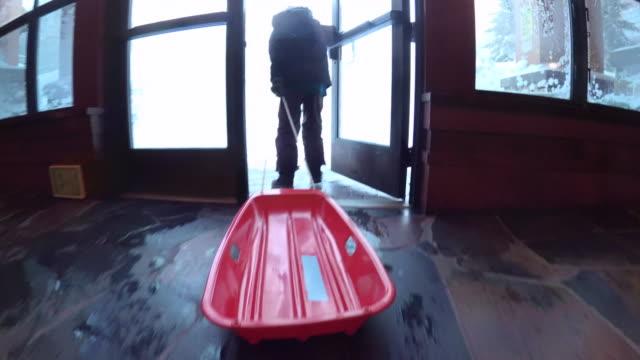 vídeos de stock e filmes b-roll de a boy pulls his red sled to go sledding in the snow. - roupa de esqui