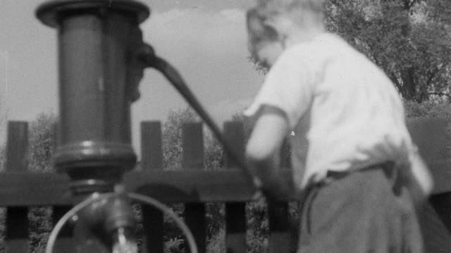 1937 ms boy pumping water from well into bucket / essex, england - water pump stock videos & royalty-free footage