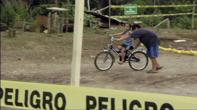 ws boy pushes sister on bicycle in cordoned off area / ecuador - sister stock videos & royalty-free footage