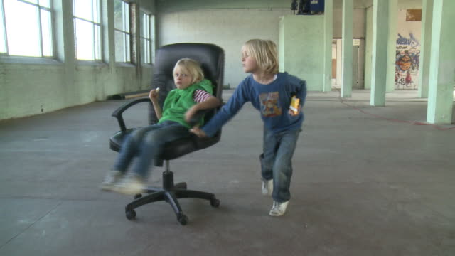 MS boy (8-9) pushing boy (6-7) on armchair in empty warehouse, Gent, Belgium